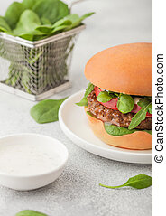 Healthy vegetarian meat free burger on round chopping board with vegetables and spinach on light table background with organic sauce.