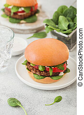 Healthy vegetarian meat free burgers on round ceramic plate with vegetables and spinach on light table background with glass of water.