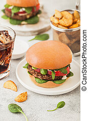 Healthy vegetarian meat free burgers on round ceramic plate with vegetables on light table background with potato wedges and glass of cola. Top view.