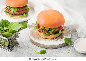 Healthy vegetarian meat free burgers on round chopping board with vegetables and spinach on light table background and organic sauce.