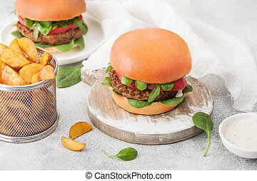 Healthy vegetarian meat free burgers on round chopping board with vegetables on light table background with potato wedges. Top view