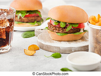 Healthy vegetarian meat free burgers on round chopping board with vegetables on light table background with potato wedges and glass of cola. Top view.