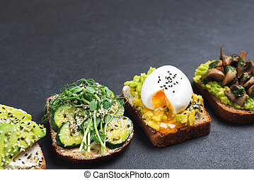 Healthy vegetarian toasts with avocado on black background