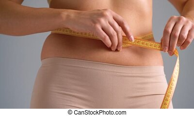 Healthy waist with measuring tape - Woman measures the waist...