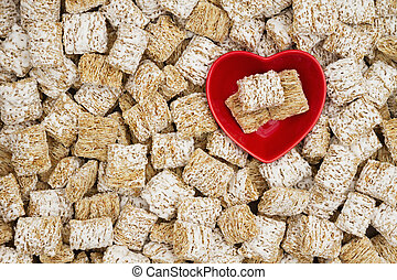 Healthy whole grain cereal background with a heart bowl