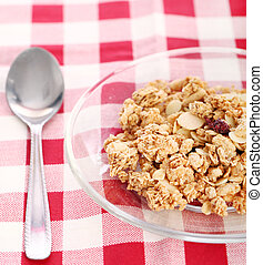 Healthy wholegrain muesli in a plate with silver spoon on a squared tablecloth