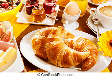 Healthy wholesome breakfast with two fresh croissants on a plate with a boiled egg, fresh fruit and cheese, cereal and a cup of coffee, focus to the croissants