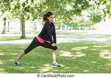 Healthy woman doing stretching exercise in park