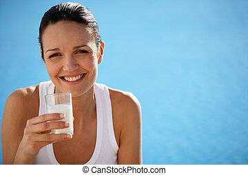 Healthy woman drinking a glass of milk