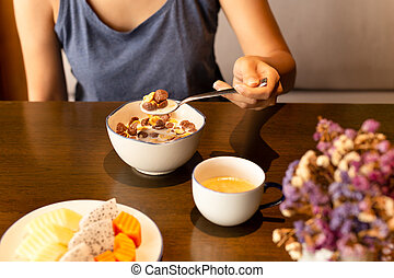 Healthy woman eating corn flakes cereal and coffee for breakfast on table.