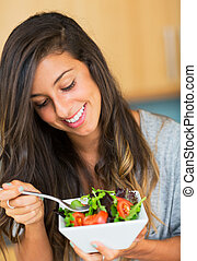 Healthy woman eating salad
