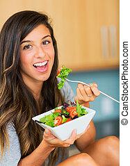 Healthy woman eating salad