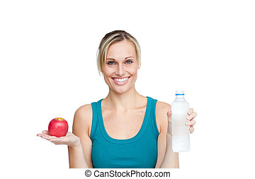 healthy woman holding an apple and a bottle of water against a white background smiling at the camera