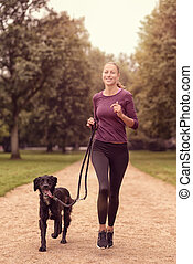 Healthy Woman Jogging in the Park with her Dog - Full length...