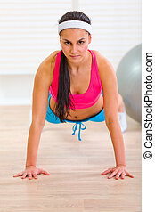 Healthy woman making push-up exercises at home