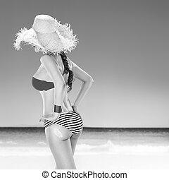 healthy woman on beach applying sun cream