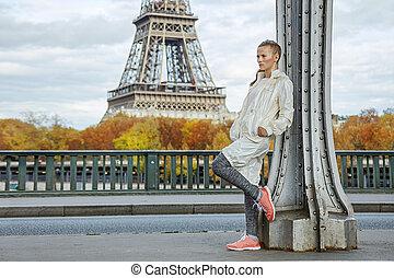 healthy woman on Pont de Bir-Hakeim bridge looking into...