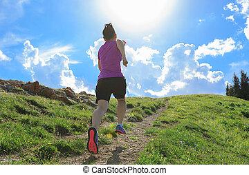 healthy woman running on beautiful mountain peak