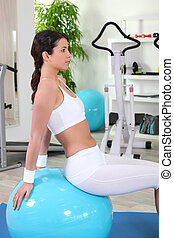 Healthy woman sitting on fitness ball