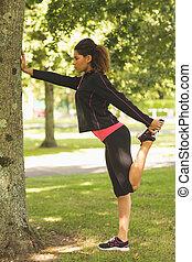 Healthy woman stretching her leg du