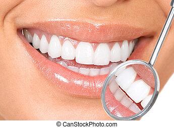 teeth - Healthy woman teeth and a dentist mouth mirror