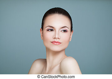 Healthy Woman with Cute Face and Clear Skin on Blue Background. Young Beauty