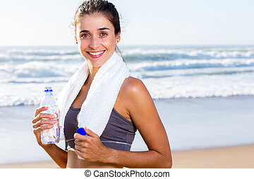 healthy woman with towel and water bottle after exercise on...