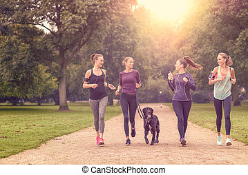 Healthy Women Jogging at the Park with a Dog - Four Healthy...