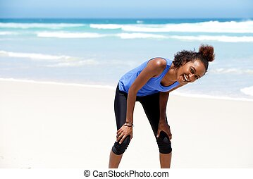 Healthy young african woman laughing at the beach