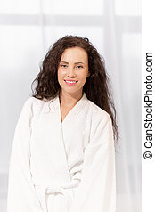 Healthy young charming woman with toothy smile wearing white soft bathrobe