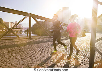 healthy young couple jogging in the city