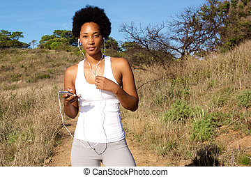 Healthy young female runner having break and listening to music