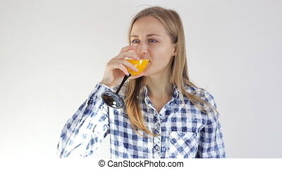 Healthy young girl drinks orange juice. Young woman with a glass of juice