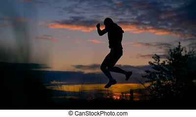 Healthy young man jumping at sunset