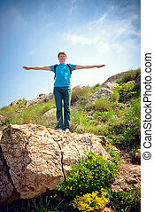 healthy young man on a hill in the mountains