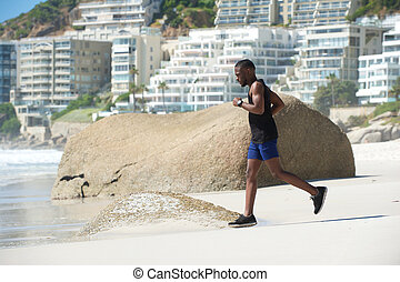 Healthy young man running on beach