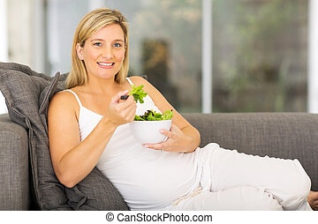 young pregnant woman eating green salad
