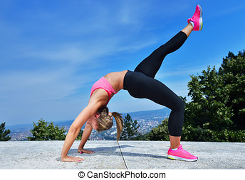healthy young pretty woman stretching her leg during exercise in park.