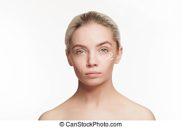 Healthy young skin. Young woman with healthy skin and drops of cream on face