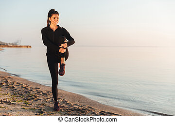 Healthy young sportswoman doing stretching exercises