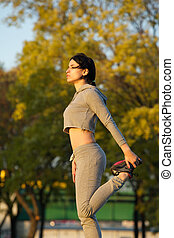Healthy young woman doing exercise outdoors in park