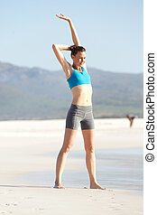 Healthy young woman doing stretching exercise at the beach