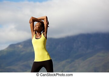 Healthy young woman doing stretching workout in nature