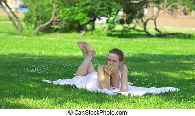 Healthy young woman eating green apple and smiling