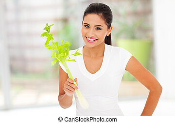 young woman holding celery stick
