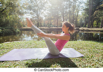Young Woman Performing Seated Yoga Asana Boat Pose - Healthy...