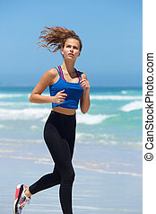 Healthy young woman running by the sea