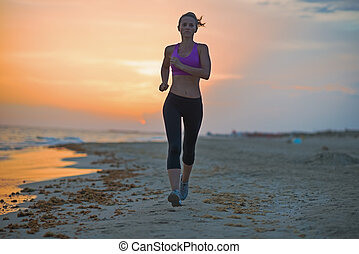 Healthy young woman running on beach in the evening