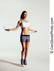 Healthy young woman skipping rope in studio