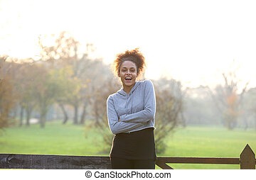 Healthy young woman standing in nature smiling